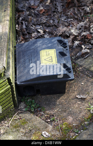 Roguard rodent bait do not touch danger poison in garden by decking - Stock Photo