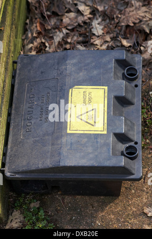 Roguard rodent bait do not touch danger poison in garden in UK - rat bait box pest control - Stock Photo