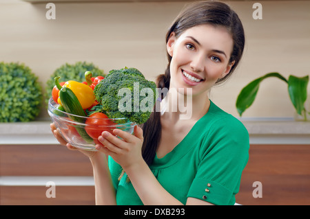 woman in kitchen making salad - Stock Photo