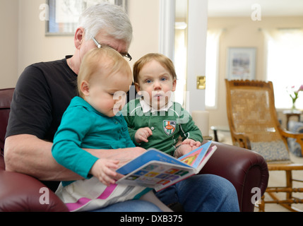 Boy and girl twin children sitting on grandfathers lap reading a story book at home - Stock Photo