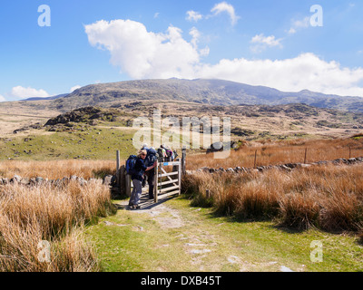 Ramblers walking through gate on Rhyd Ddu path up Mount Snowdon with peak in distance in Snowdonia National Park - Stock Photo