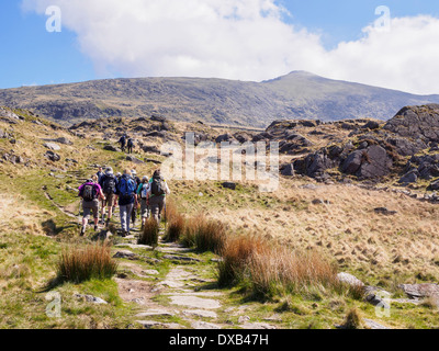 Group of Ramblers walking on Rhyd Ddu path up Mt Snowdon with view to peak in distance in Snowdonia National Park - Stock Photo