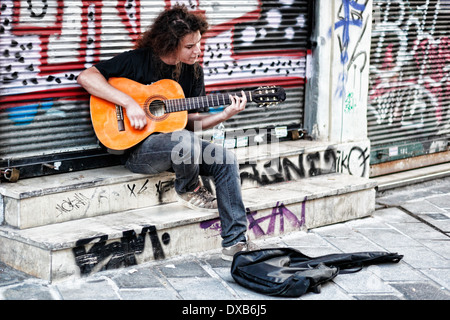 A musician playing guitar in the street of Athens, Greece - Stock Photo