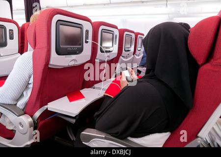 Muslim arab woman in a burka using her mobile phone on a Virgin Atlantic plane flying from Dubai to London UK - Stock Photo