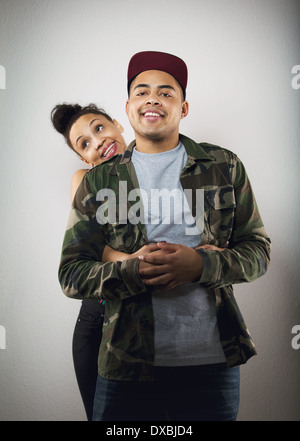 Cute young woman holding her boyfriend from behind on grey background. Cute young couple in love. - Stock Photo
