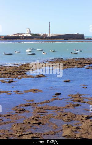 Fishing boats in front of the Castle of San Sebastián, Cádiz, Spain. - Stock Photo