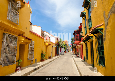 Typical street scene in Cartagena, Colombia of a street with old historic colonial houses on each side of it - Stock Photo