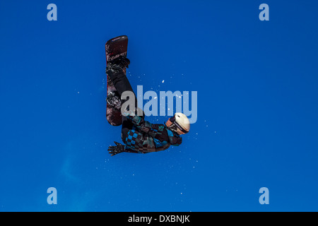 Snowboarder travelling through the air - Stock Photo