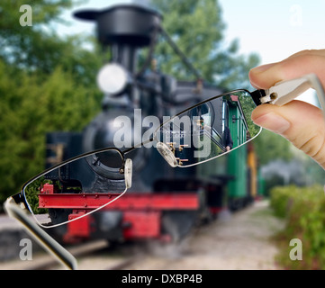 Man is viewing to vintage train on display through eyeglasses - Stock Photo