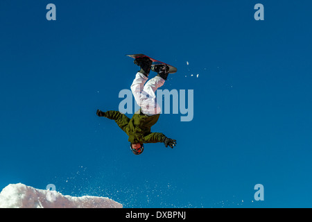 Person learning to snowboard jump: Airborne snowboarder upside down after taking off on a jump - Stock Photo