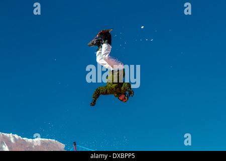 Airborne snowboarder about to land in a heap on a giant airbag - Stock Photo
