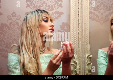 pretty young woman spraying herself with perfume from small bottle in front of large mirror - Stock Photo