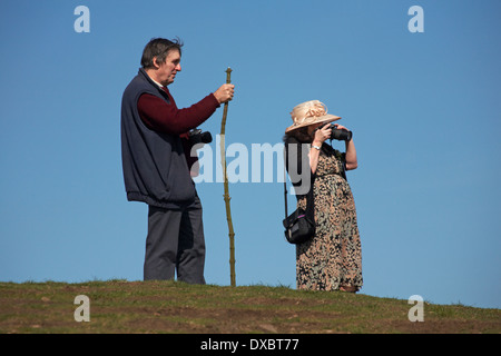 man and woman, part of wedding party, taking photos at The Beacon in the Malvern Hills, Great Malvern in April - Stock Photo