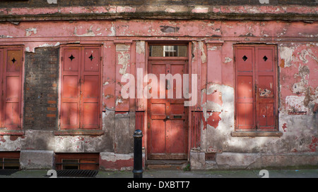 Historic Huguenot derelict pink front of building house facade with shutters on Princelet St. in Spitalfields East - Stock Photo