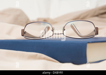 Detail photo showing a pair of glasses and a book sitting on bed - Stock Photo
