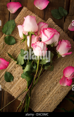 Pink roses on burlap ready to arrange shot from above - Stock Photo