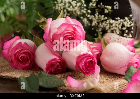 Pink roses with baby's breath on burlap ready to arrange - Stock Photo