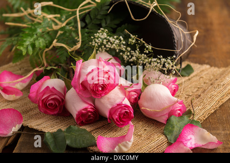 Pink roses on burlap and metal bucket ready to arrange - Stock Photo