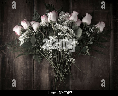 Desaturated bouquet arrangement of pink roses and baby's breath on rustic wood shot from above - Stock Photo