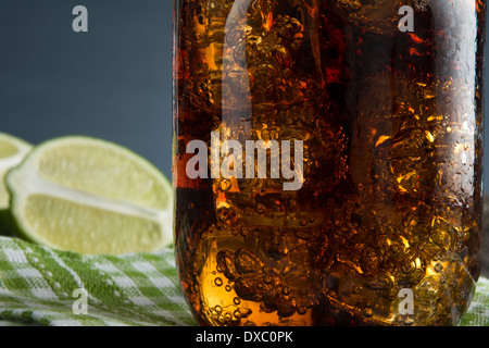 Closeup of Cuba Libre or rum and cola drink with ice and lime in mason jar - Stock Photo