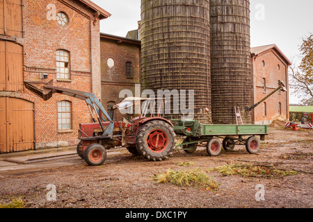 Tractor and trailer parked in a farmyard in front of a large multistorey barn and cylindrical silos with a famer - Stock Photo