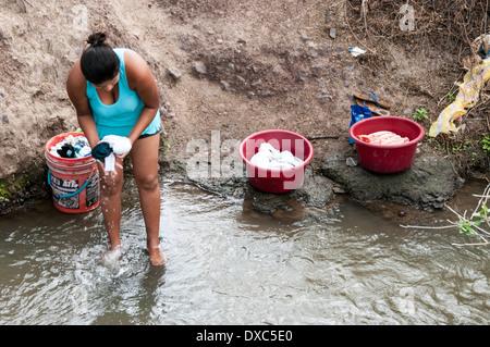 Peruvian woman washing clothes in the river.Piura, Peru. - Stock Photo