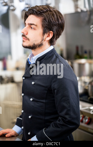 Attractive smiling cook or chef stirring a huge stainless steel pot of stew or casserole on a hob in a commercial - Stock Photo
