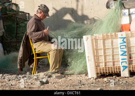 fisherman sitting repairing fishing nets - Stock Photo