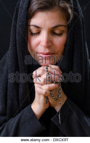 Hispanic woman having her daily devotional with God. Religious life. Worship and adoration of a pious woman - Stock Photo