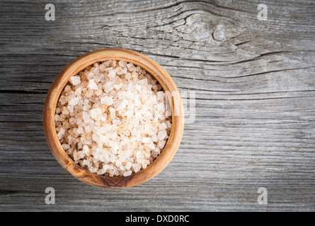 Pink salt in the wooden bowl, on wooden board - Stock Photo