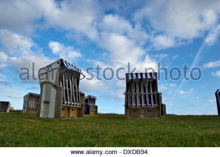 Strandkörbe, AKA beach chairs, sit closed up on a grassy knoll on Insel Norderney. - Stock Photo