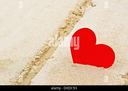 Red paper heart in beach sand, summer romance concept. - Stock Photo