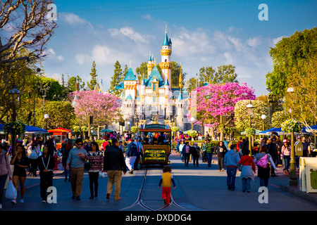 Disneyland Main Street crowded with guests and a tram car in the road leading towards the iconic pink castle. - Stock Photo