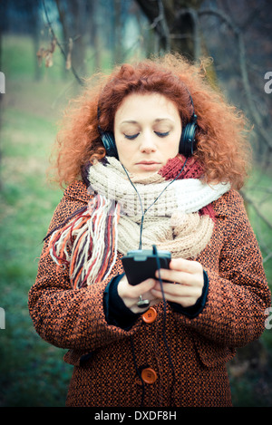 young beautiful red curly hair woman listning music at the park - Stock Photo