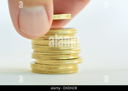 Male hand counting and stacking gold coins isolated on white background. - Stock Photo
