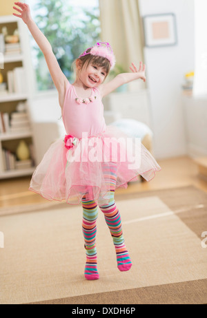 Girl (4-5) wearing tutu dancing in living room - Stock Photo