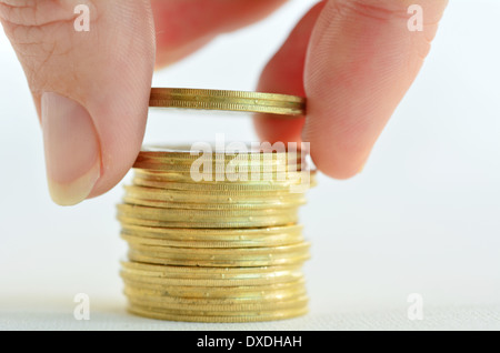 Female hand counting and stacking gold coins isolated on white background. - Stock Photo