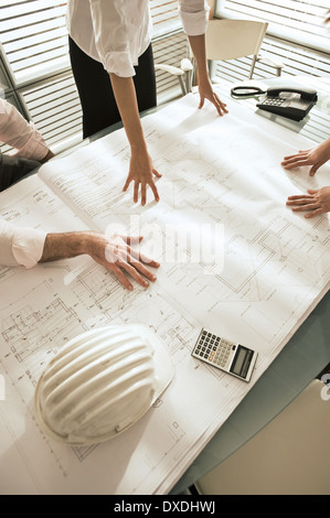 Closeup of professionals looking at architectural plans on desk - Stock Photo