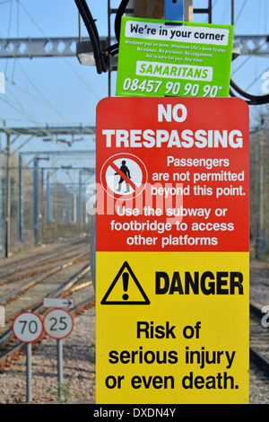 Samaritans contact notice wedged into the top of warning signs on station platform beside railway tracks - Stock Photo