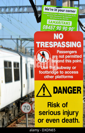 Samaritans contact notice wedged into the top of warning signs on station platform with train passing - Stock Photo