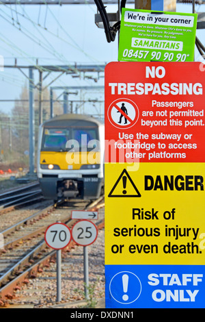 Samaritans contact notice wedged into the top of warning signs on station platform with train approaching - Stock Photo