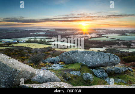 A frosty early spring sunrise looking out over a patchwork of fields and rolling hills at Helman Tor a rocky outcrop - Stock Photo