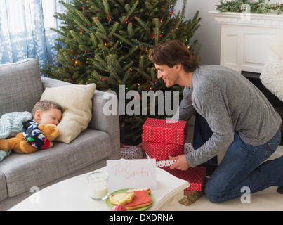 Man giving presents under Christmas tree while his son (6-7) sleeping - Stock Photo