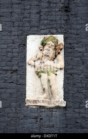 Figure of man with green leaf covering on a wall in Amsterdam the Netherlands - Stock Photo