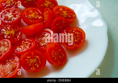 Cherry tomatoes on a plate, cut in two halves. Close view. - Stock Photo
