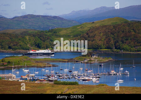 M.V.Clansman passes ardentrive marina and Dunollie Castle as she enters Oban Bay, Argyll - Stock Photo