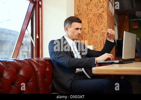 Businessman sitting and using laptop at office - Stock Photo
