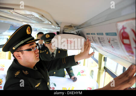 Qingdao, China's Shandong Province. 25th Mar, 2014. Policemen stick fire-safety posters inside a school bus in Qingdao, - Stock Photo