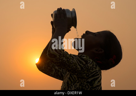 India, Uttar Pradesh, Agra,silhouette of girl drinking from water jug at sunset. - Stock Photo