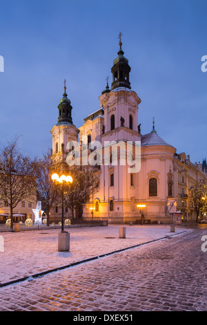 the Church of St Nicholas with a smattering of snow and Christmas lights in the Old Town Square, Prague, Czech Republic - Stock Photo